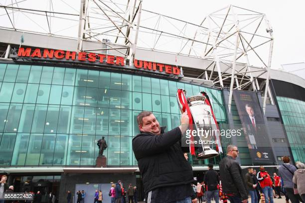 Manchester United fan poses with a trophy outside the stadium prior to the Premier League match between Manchester United and Crystal Palace at Old...