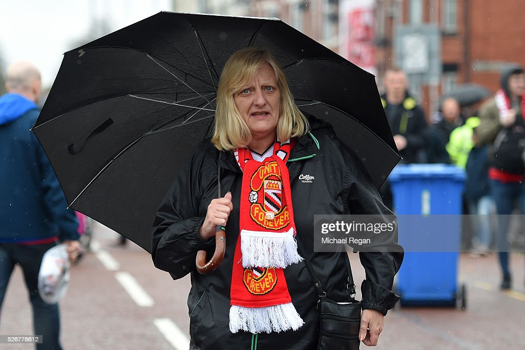 A Manchester United fan shelters from the rain prior to the Barclays Premier League match between Manchester United and Leicester City at Old Trafford on May 1, 2016 in Manchester, England.