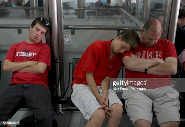 Manchester United fans asleep as they wait for their flight inside Rome's Ciampino Airport