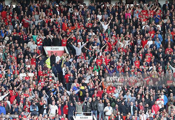 Manchester United fans celebrate Wayne Rooney scoring their first goal during the Premier League match between Manchester United and Swansea City at...