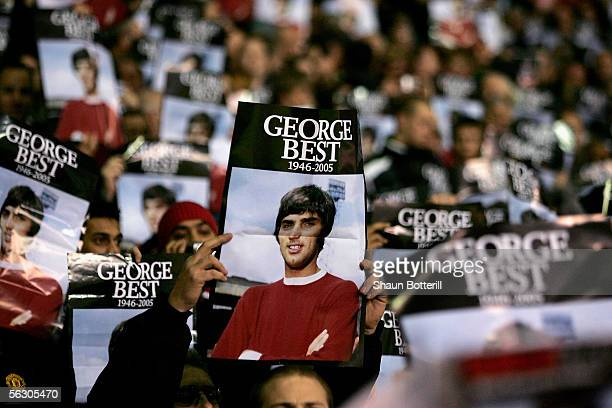 Manchester United fans hold up posters of the late George Best prior to the Carling Cup match between Manchester United and West Bromwich Albion at...