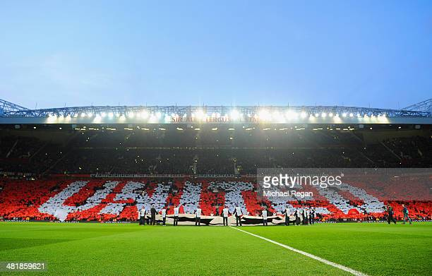 Manchester United fans lift cards to display the word 'United' during the UEFA Champions League Quarter Final first leg match between Manchester...