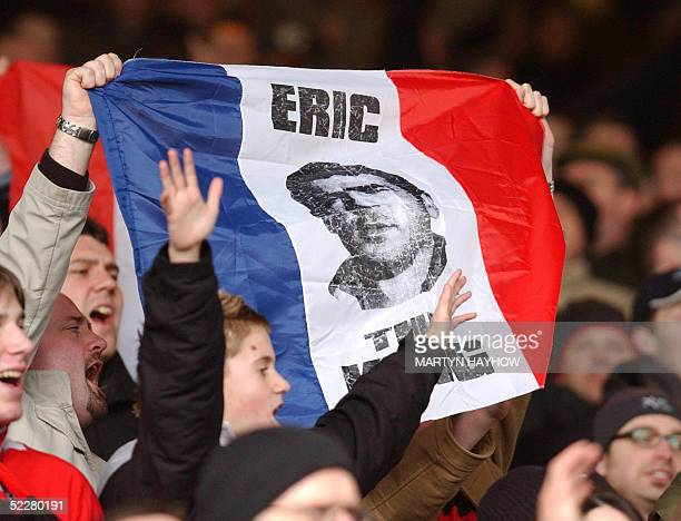 Manchester United fans wave 05 March 2005 in Londona French flag with a picture of former Manchester United striker frenchman Eric Cantona ten years...