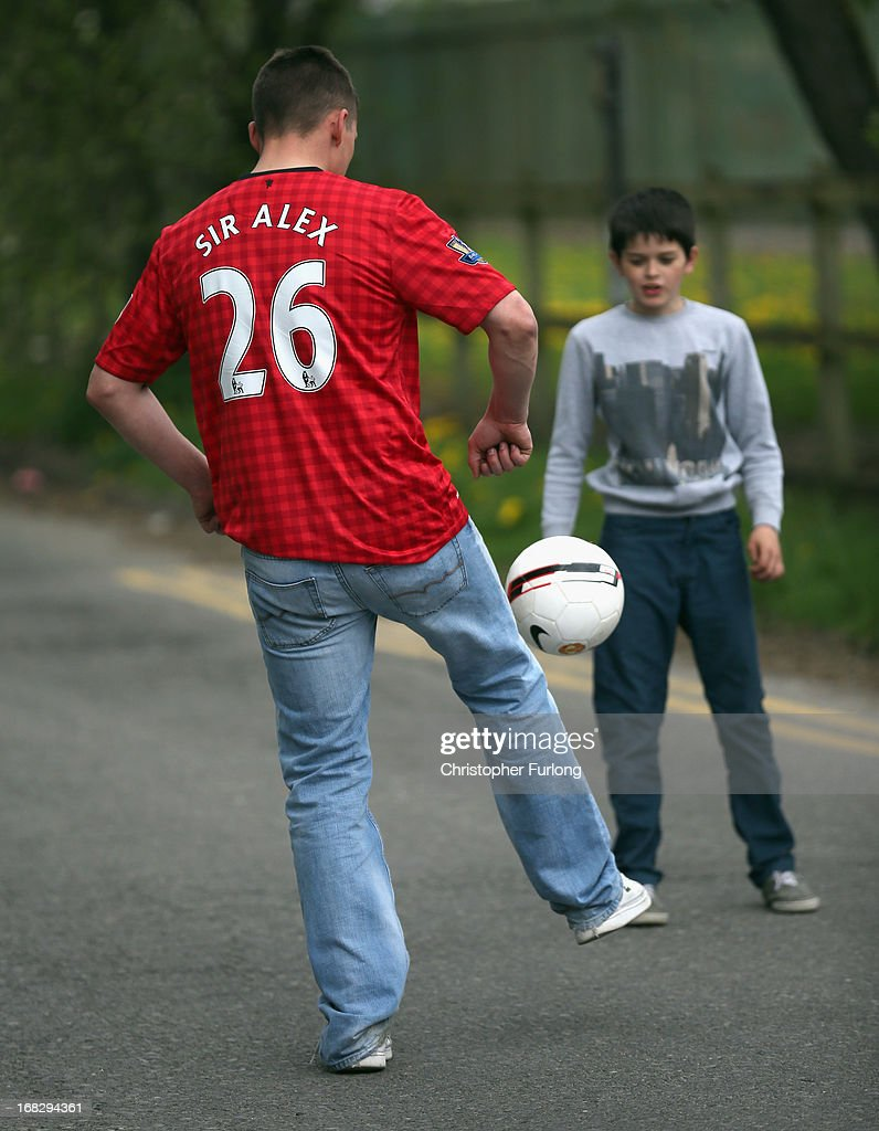 A Manchester United football fan wears a club shirt adorned with 'Sir Alex 26' at the entance to the club's Carrington Training Ground on May 8, 2013 in Manchester, England. Sir Alex Ferguson announced today that he is retiring as manager of Manchester United after 26 years.