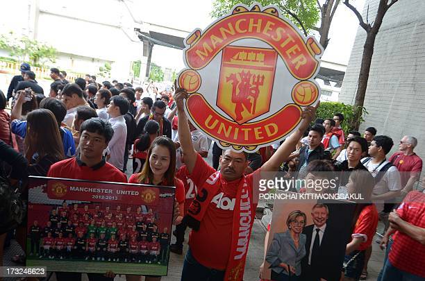 Manchester United football fans hold posters as team players arrive at Don Muang International airport in Bangkok on July 11 2013 Manchester United...