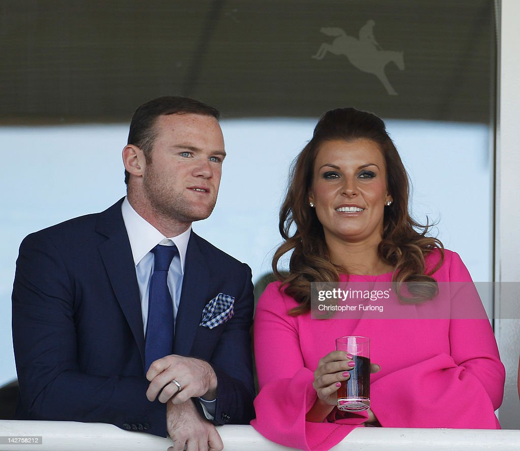 Manchester United football player <a gi-track='captionPersonalityLinkClicked' href=/galleries/search?phrase=Wayne+Rooney&family=editorial&specificpeople=157598 ng-click='$event.stopPropagation()'>Wayne Rooney</a> and his wife Coleen watch the racing during the first day of the Aintree Grand National meeting on April 12, 2012 in Aintree, England. The first day, known as Liverpool Day, celebrates the city's link with the famous Aintree Racecourse.