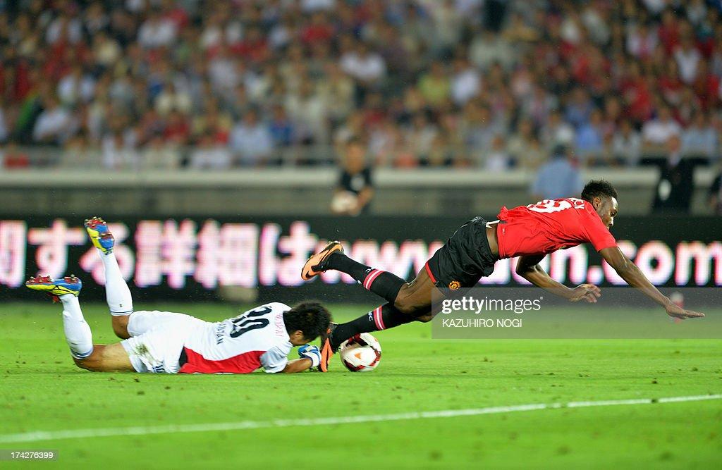 Manchester United forward Danny Welbeck (R) falls on the ground after colliding with Yokohama F Marinos goalkeeper Yuji Rokutan (R) during their friendly football match at Nissan Stadium in Yokohama on July 23, 2013.
