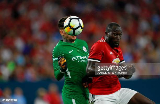 Manchester United forward Romelu Lukaku hits a header past Manchester City goalkeeper Ederson Moraes during the International Champions Cup soccer...