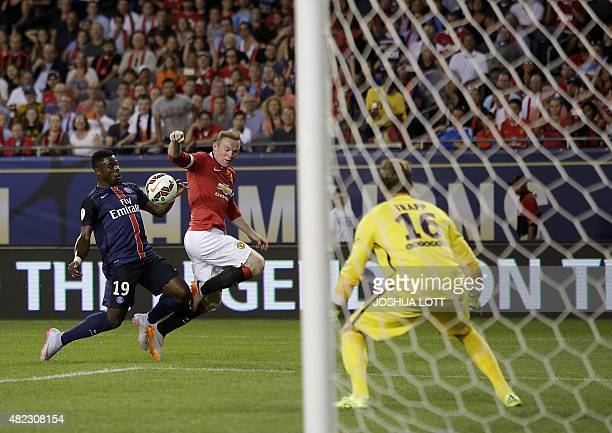 Manchester United forward Wayne Rooney battles for the ball with Paris SaintGermain defender Serge Aurier as Paris SaintGermain goalkeeper Kevin...