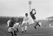 Manchester United goalkeeper Jimmy Rimmer catches the ball ahead of Paul Madeley of Leeds United during their Division One match played at Elland...