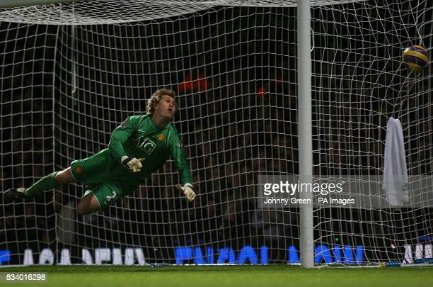 Manchester United goalkeeper Tomasz Kuszczak attempts to save the shot as West Ham United's Matthew Upson scores their second goal
