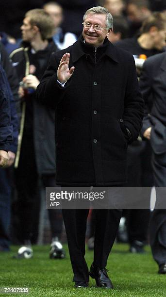 Manchester United manager Sir Alex Ferguson waves to fans prior to kick off against Portsmouth during their English Premiership football match at Old...