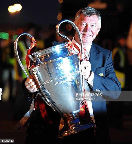 Manchester United manager Alex Ferguson holds the Campions League trophy on May 22 2008 as he returns to Manchester Airport from Moscow after beating...