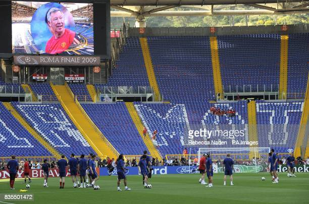Manchester United manager Alex Ferguson is displayed on the big screen as the players train