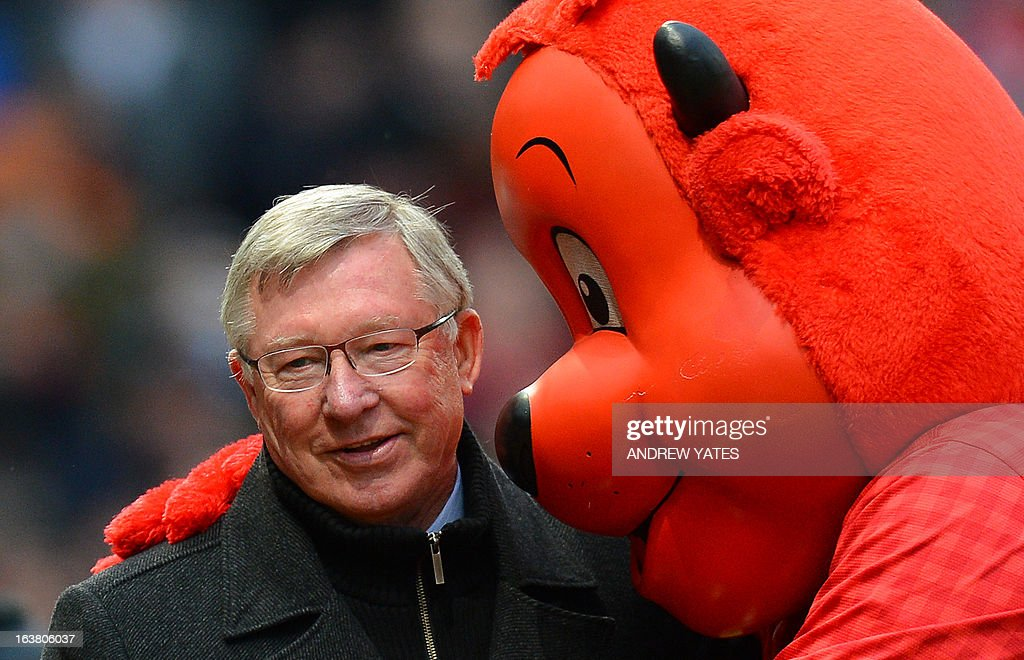 "Manchester United manager Alex Ferguson (L) is hugged by mascot Fred The Red as he makes his way to the bench before the English Premier League football match between Manchester United and Reading at Old Trafford in Manchester, north-west England on March 16, 2013. Manchester United won 1-0. AFP PHOTO/ANDREW YATES RESTRICTED TO EDITORIAL USE. No use with unauthorized audio, video, data, fixture lists, club/league logos or ""live"" services. Online in-match use limited to 45 images, no video emulation. No use in betting, games or single club/league/player publications."