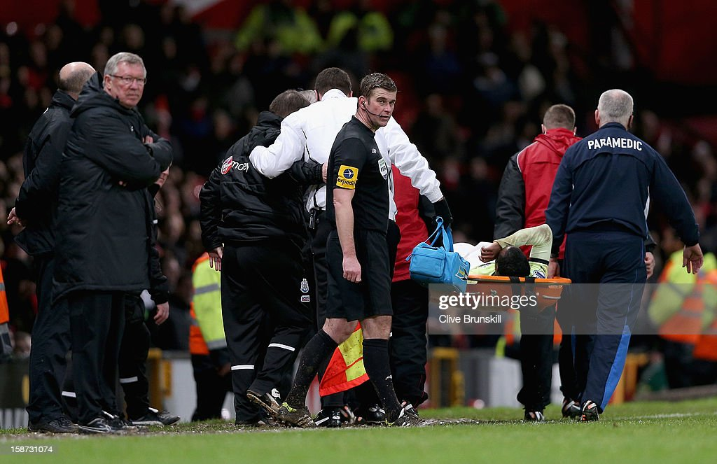 Manchester United manager Alex Ferguson watches from the sideline as Vurnon Anita is carried off on the stretcher after being treated on the pitch after a bad collision during the Barclays Premier League match between Manchester United and Newcastle United at Old Trafford December 26, 2012 in Manchester, England.