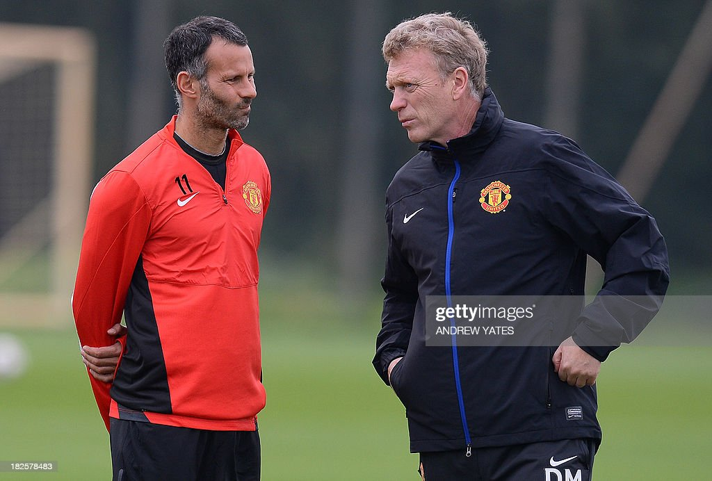 Manchester United manager David Moyes (R) speaks to Manchester United's Welsh midfielder Ryan Giggs during a training session at the team's Carrington training complex in Manchester, north-west England on October 1, 2013, on the eve of their UEFA Champions League group A football match against Shakhtar Donetsk in the Ukraine. AFP PHOTO/ANDREW YATES
