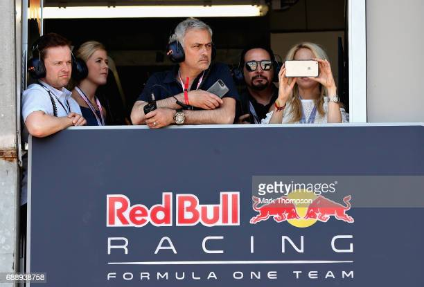 Manchester United manager Jose Mourinho of Portugal watches the action from the Red Bull Racing garage with Declan Donnelly during qualifying for the...