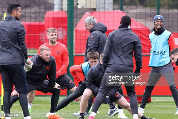 Manchester United manager Jose Mourinho walks past players Wayne Rooney Luke Shaw and Michael Carrick during the training session at the Aon Training...