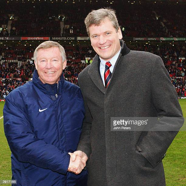 Manchester United manager Sir Alex Ferguson and Chief Executive David Gill pose on the pitch to celebrate Ferguson's new contract ahead of the FA...