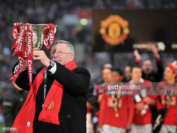 Manchester United manager Sir Alex Ferguson celebrates with the trophy after his team beat Aston Villa 21 to win the 2010 Carling Cup Final at...