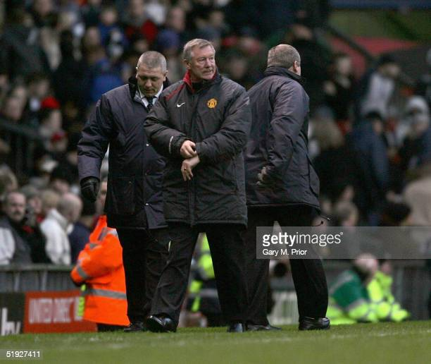 Manchester United manager Sir Alex Ferguson nervously checks his watch during the FA Cup third round match between Manchester United and Exeter City...