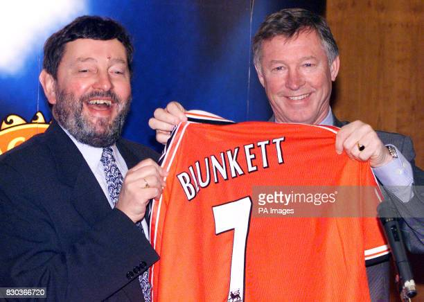 Manchester United manager Sir Alex Ferguson presents Education Secretary David Blunkett with a personalised football shirt during a visit to open the...