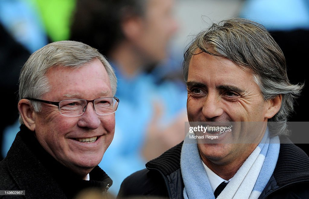 Manchester United Manager Sir Alex Ferguson smiles with Manchester City Manager Roberto Mancini (R) prior to the Barclays Premier League match between Manchester City and Manchester United at the Etihad Stadium on April 30, 2012 in Manchester, England.