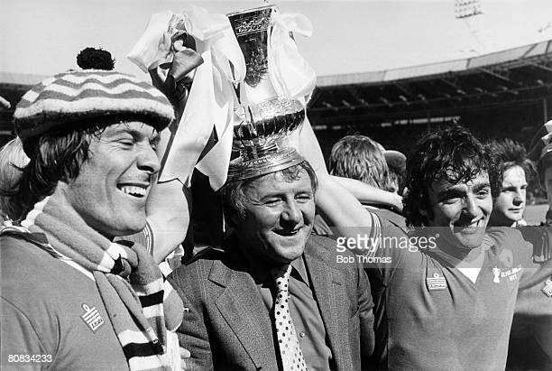 Manchester United manager Tommy Docherty centre celebrates with goalscorers Stuart Pearson left and Lou Macari after United had beaten Liverpool 21...