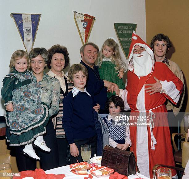 Manchester United manager Tommy Docherty joins Santa Claus and some of the guests at the club's Christmas Party at Old Trafford in Manchester circa...