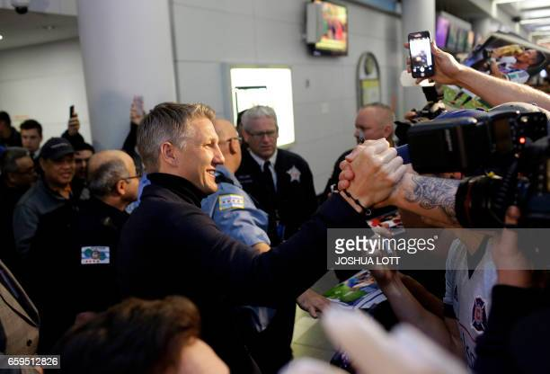 Manchester United midfielder Bastian Schweinstiger greets fans as he arrives at O'hare International Airport on March 28 2017 in Chicago Illinois...