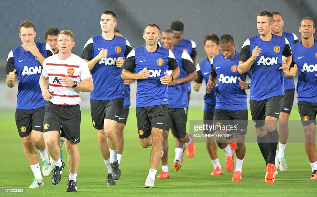 Manchester United midfielder Ryan Giggs (C) and his teammates warm up during a training session at Nissan Stadium in Yokohama, suburban Tokyo on July 22, 2013. The United will play Yokohama F Marinos on July 23 and then face J-League club Cerezo Osaka at Nagai Stadium on July 26.