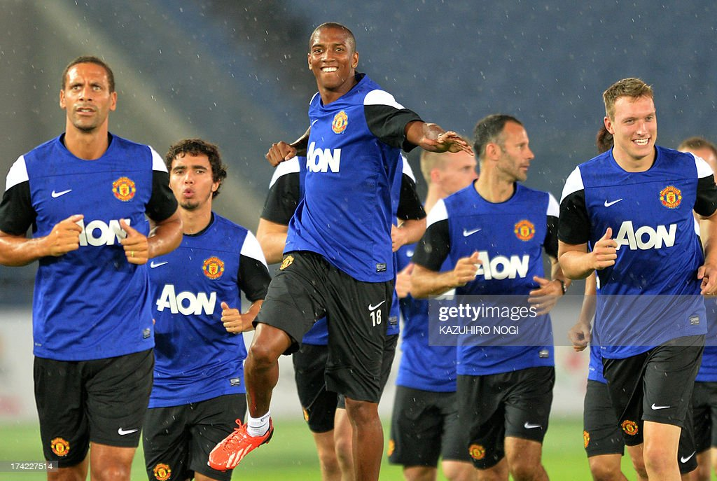 Manchester United player Ashley Young (C) and his teammates warm up during a training session at Nissan Stadium in Yokohama, suburban Tokyo on July 22, 2013. The United will play Yokohama F Marinos on July 23 and then face J-League club Cerezo Osaka at Nagai Stadium on July 26.