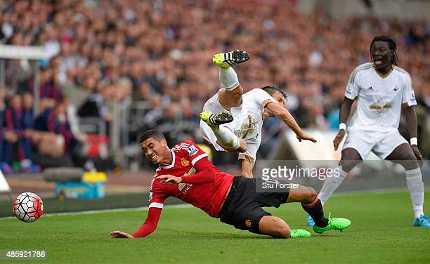 Manchester United player Chris Smalling challenges Jack Cork of Swansea during the Barclays Premier League match between Swansea City and Manchester...