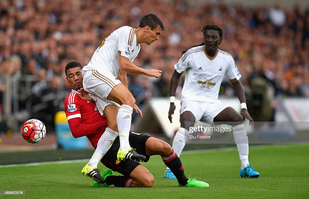 Manchester United player <a gi-track='captionPersonalityLinkClicked' href=/galleries/search?phrase=Chris+Smalling&family=editorial&specificpeople=5964313 ng-click='$event.stopPropagation()'>Chris Smalling</a> (l) challenges <a gi-track='captionPersonalityLinkClicked' href=/galleries/search?phrase=Jack+Cork&family=editorial&specificpeople=4206991 ng-click='$event.stopPropagation()'>Jack Cork</a> of Swansea during the Barclays Premier League match between Swansea City and Manchester United on August 30, 2015 in Swansea, United Kingdom.