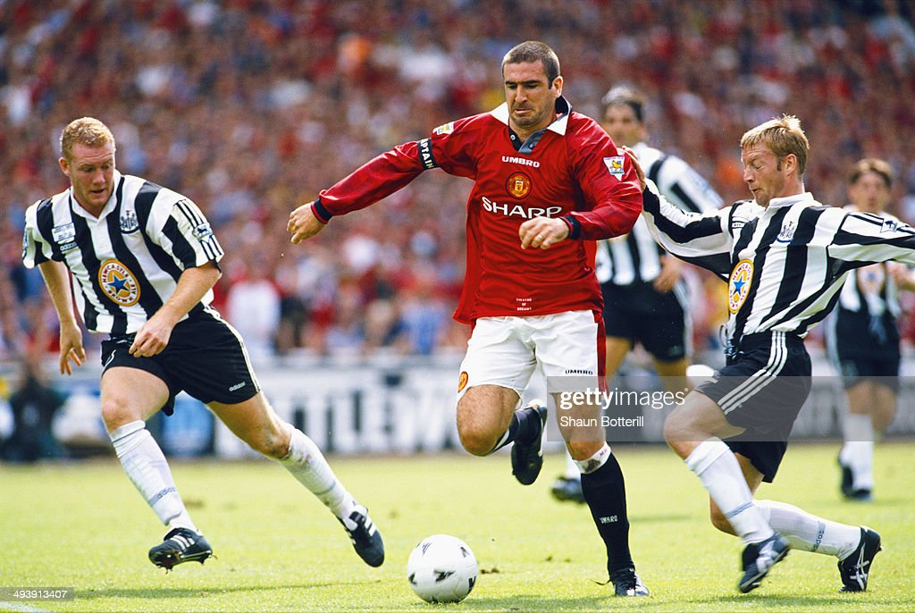 Manchester United player Eric Cantona (c) beats Steve Watson and David Batty (r) during the FA Charity Shield match between Manchester United and Newcastle United at Wembley Stadium on August 11, 1996 in London, England.