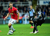 Manchester United player Jonny Evans in action as Papiss Cisse of Newcastle looks on during the Barclays Premier League match between Newcastle...