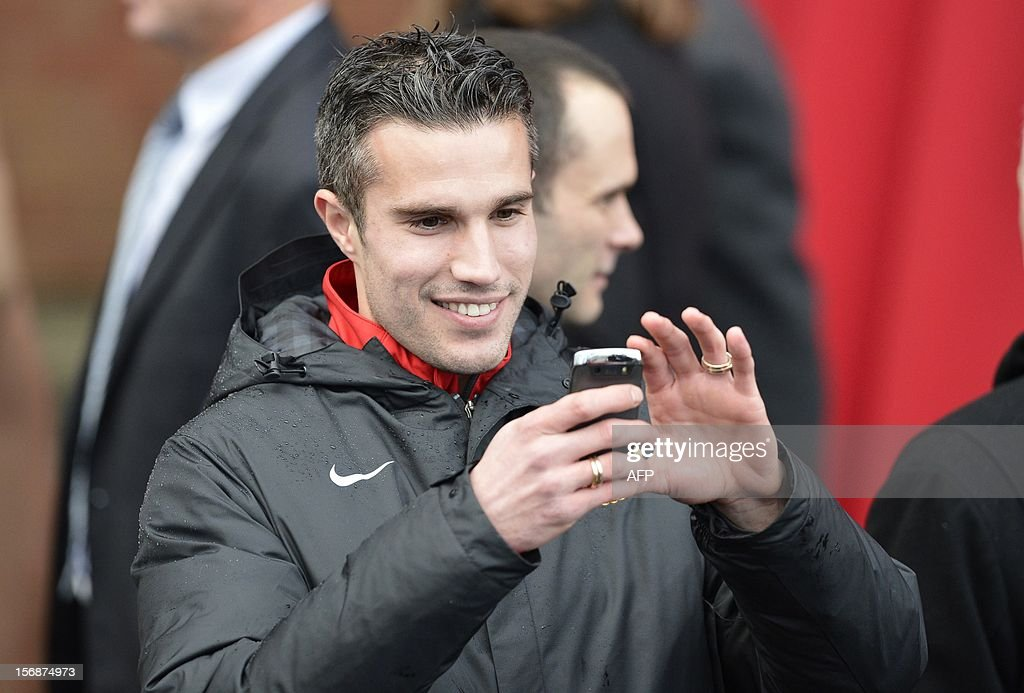 Manchester United player Robin Van Persie takes a photograph during the unveiling of a statue of Manchester United's manager Alex Ferguson at Old Trafford stadium in Manchester, northern England on November 23, 2012. Manchester United manager Alex Ferguson quipped that he was 'out-living death' after a bronze statue of him was unveiled outside Old Trafford. The nine-foot statue was commissioned in November last year to mark Ferguson's 25th anniversary at the club, when the North Stand was renamed in his honour. AFP PHOTO/POOL/ Nigel Roddis