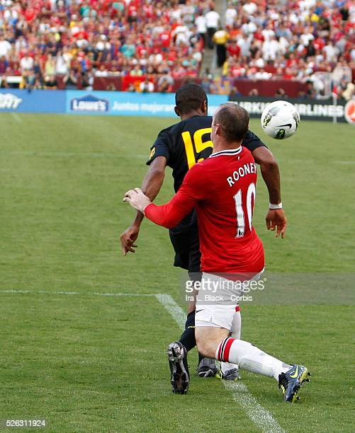 Manchester United player Wayne Rooney tries to stop the advance of FC Barcelona player Seydou Keita during the World Football Challenge Friendly...