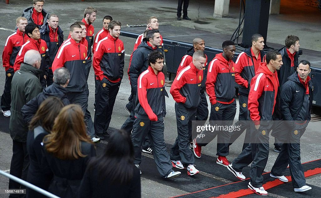 Manchester United players arrive for the unveiling of a statue of Manchester United's manager Alex Ferguson at Old Trafford stadium in Manchester, northern England on November 23, 2012. Manchester United manager Alex Ferguson quipped that he was 'out-living death' after a bronze statue of him was unveiled outside Old Trafford. The nine-foot statue was commissioned in November last year to mark Ferguson's 25th anniversary at the club, when the North Stand was renamed in his honour. AFP PHOTO/POOL/ Nigel Roddis
