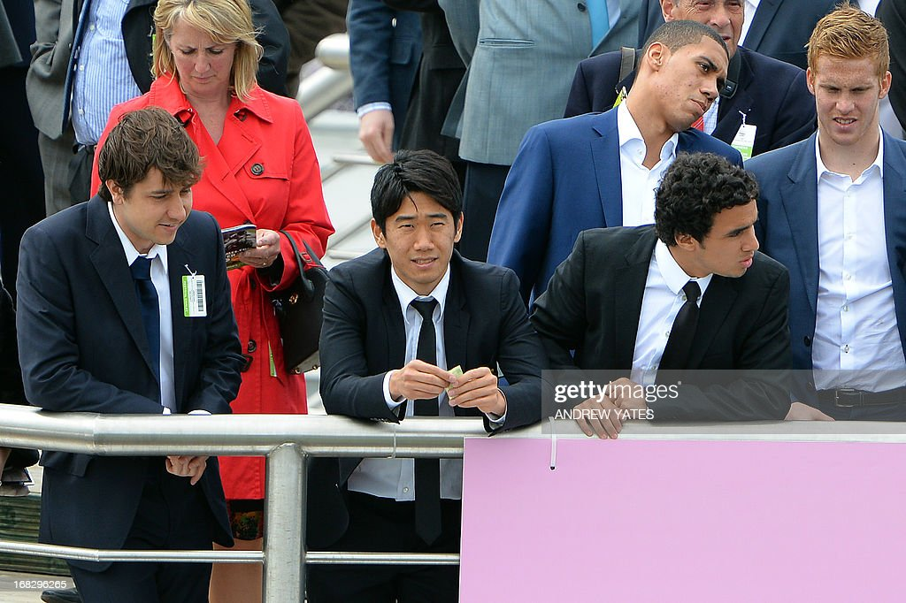 Manchester United players Brazilian defender Rafael (R) and Japanese midfielder Shinji Kagawa (C) watch the action at the Chester Races horse racing event at Chester Racecourse in Cheshire, northwest England on May 8, 2013. Alex Ferguson will retire as Manchester United boss at the end of the season, the Premier League champions announced on May 8, ending the most successful managerial reign in English football.