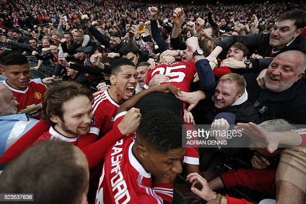 Manchester United players celebrate with the crowd including Manchester United's English midfielder Jesse Lingard Manchester United's English...