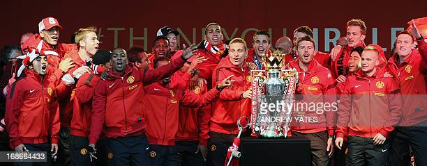 Manchester United players celebrate with the Premier League trophy after winning the title for the 13th time during their victory parade outside the...
