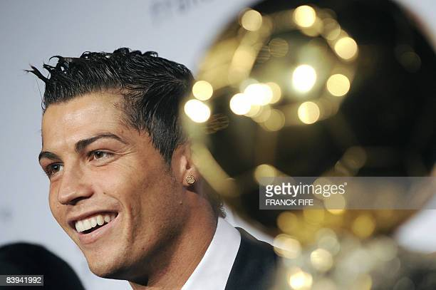 Manchester United Portuguese winger Cristiano Ronaldo smiles next to his trophy after he received the European footballer of the year award the...