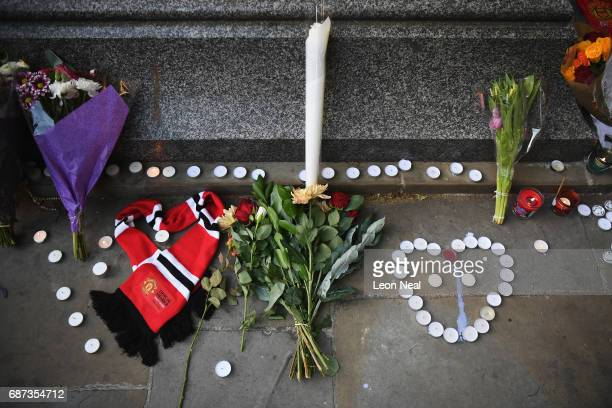 Manchester United scarf laid in the shape of a heart lies next to flowers left by members of the public at a candlelit vigil to honour the victims of...