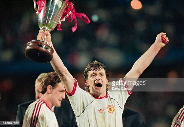 Manchester United striker Mark Hughes celebrates with the trophy as Steve Bruce looks on after the 1991 European Cup Winners Cup Final between...