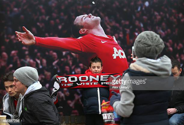 Manchester United supporter takes a picture of her son in front of an image of Wayne Rooney outside Old Trafford prior to the Barclays Premier League...