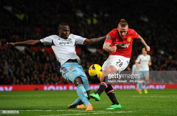 Manchester United's Alexander Buttner and West Ham United's Guy Demel battle for the ball