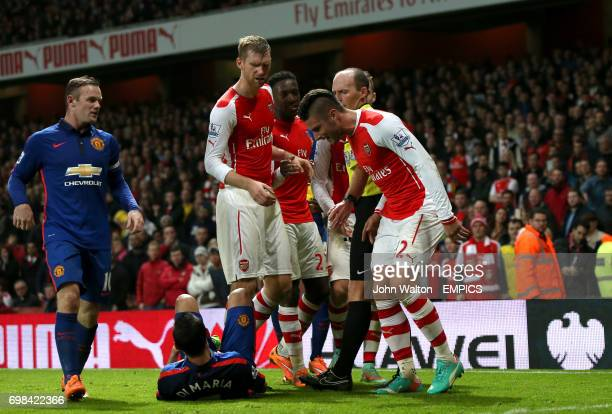 Manchester United's Angel Di Maria lies on the ground injured as Arsenal players argue with referee Mike Dean
