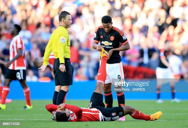 Manchester United's Anthony Martial helps Southampton's Virgil van Dijk as he lies injured with cramp